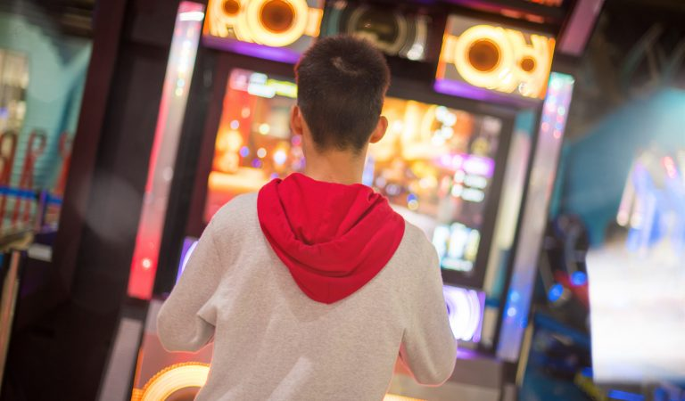 A boy dancing with game arcade machine in selective focus.